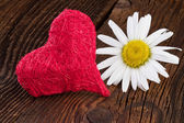 Red heart and chamomile flower on old wooden background — Stock Photo