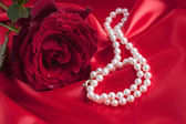 Red Rose with Pearl Necklace on a Red Silk — Stock fotografie