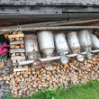 Old milk cans and firewood in a alpine hut — Stock Photo