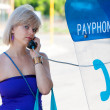 Woman on a payphone — Stock Photo