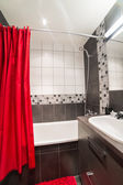 Modern bathroom with red curtains — Stock Photo