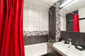 Modernes badezimmer mit waschbecken und roten vorhängen — Stockfoto