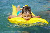 Happy young boy smiling at the swimming pool on a yellow lilo — Stock Photo