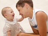 Smiling teen brother and baby sister — Stock Photo