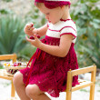 Toddler girl in hand made dress tasting cherries — Stock Photo