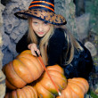 Happy young witch with a pumpkin — Stock Photo