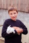 Teen boy with small white rabbit — Stock Photo