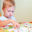 Toddler girl solving wooden puzzles — Stock Photo #39920691
