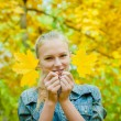 Young woman with autumn leaves near her face — ストック写真