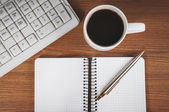 Blank notepad, keyboard, pen and coffee cup — Stock Photo