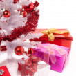 Christmas gifts near a white artificial Christmas tree — Stock Photo