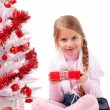 Girl sitting on the floor near a white artificial Christmas tree with gifts — Stock Photo #16514815