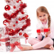 Girl sitting on the floor near a white artificial Christmas tree with gifts — Stock Photo #16514817