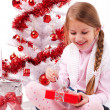 Girl sitting on the floor near a white artificial Christmas tree with gifts — Stock Photo