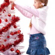 Girl decorates a white artificial Christmas tree — Stock Photo #16514833