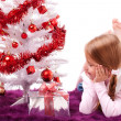 Girl lying on the carpet next to a white artificial Christmas tree with gifts — Stock Photo #16514835