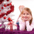 Girl lying on the carpet next to a white artificial Christmas tree with gifts — Stock Photo #16514847