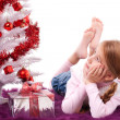 Girl lying on the carpet next to a white artificial Christmas tree with gifts — Stock Photo