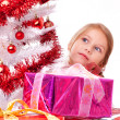 Thoughtful girl with Christmas gifts near a white artificial Christmas tree — Stock Photo #16514879