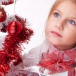Thoughtful girl with Christmas gifts near a white artificial Christmas tree — Stock Photo #16514889