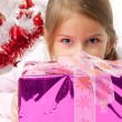 Thoughtful girl with Christmas gifts near a white artificial Christmas tree — Stock Photo #16514893