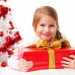Happy little girl with Christmas gifts near a white artificial Christmas tree — Foto de Stock   #16514899