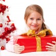 Happy little girl with Christmas gifts near a white artificial Christmas tree — Stock Photo #16514899