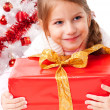 Happy little girl with Christmas gifts near a white artificial Christmas tree — Foto de Stock