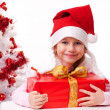 Happy little girl with Christmas gifts near a white artificial Christmas tree — Stock Photo #16514907