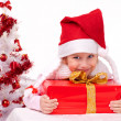 Happy little girl with Christmas gifts near a white artificial Christmas tree — Foto de Stock   #16514909