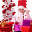 Stock Photo: Happy little girl with Christmas gifts near a white artificial Christmas tree