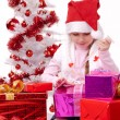 Happy little girl with Christmas gifts near a white artificial Christmas tree — Stock Photo