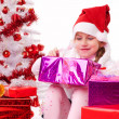 Happy little girl with Christmas gifts near a white artificial Christmas tree — Photo #16514915