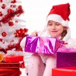 Happy little girl with Christmas gifts near a white artificial Christmas tree — Foto de Stock   #16514915