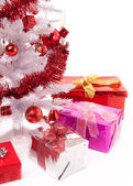 Christmas gifts near a white artificial Christmas tree — Stok fotoğraf