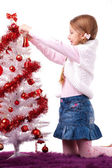 Girl decorates a white artificial Christmas tree — Stock Photo