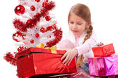Girl with Christmas gifts near a white artificial Christmas tree — Stock Photo