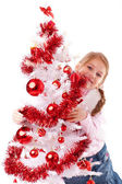 Girl embraces a white artificial Christmas tree — Stock Photo
