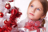 Thoughtful girl with Christmas gifts near a white artificial Christmas tree — Stock Photo