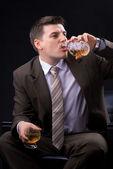Jonge zakenman zittend op een bank met een alcoholische drank — Stockfoto