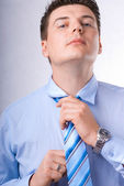 Young Businessman tying his tie — Stock Photo