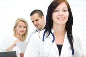 年轻的护士,同事背后的画像 — 图库照片