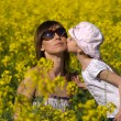 Stock Photo: Young mother and her daughter having fun at the colza field