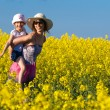 Young mother and her daughter having fun at the colza field - Stock Photo