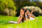 Mooie jonge vrouw met hoofdtelefoon buitenshuis — Stockfoto