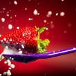 Strawberry on the spoon and milk splash - Stock Photo