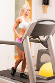 Young woman runing on a machine. — Stock Photo