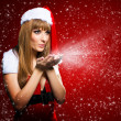 Portrait of a young Santa girl blowing stars on red background — Stock Photo