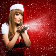 Stock Photo: Portrait of a young Santa girl blowing stars on red background