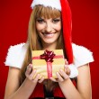Sexy woman Santa with gift boxes on red background — Stock Photo #32312545